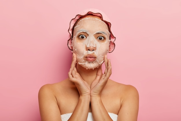 Photo of lovely asian woman has nourishing moisturizer paper mask on face, touches cheeks gently, keeps lips folded, wears pink shower cap, stands alone. skin care and beauty treatments concept