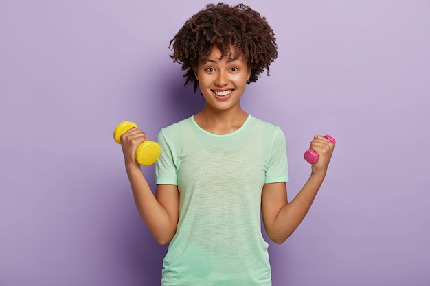 Photo of lovely cheerful strong woman raises two arms with dumbbells, trains biceps, wears casual t shirt, wants to be healthy and fit, looks happily with toothy smile. sport, women strength