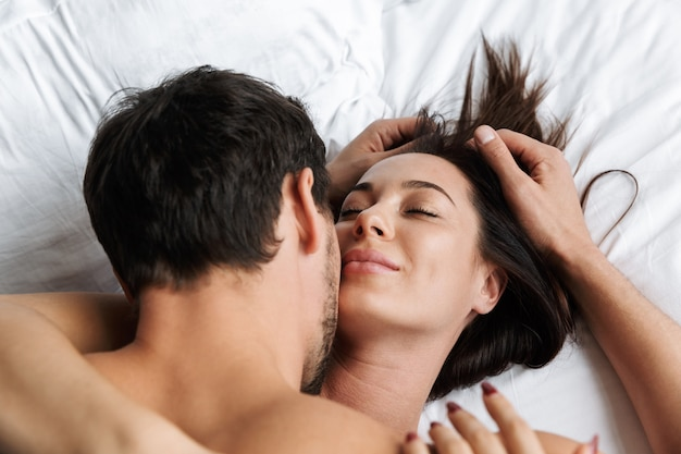 Photo of lovely couple hugging and kissing together, while lying in white bed at home