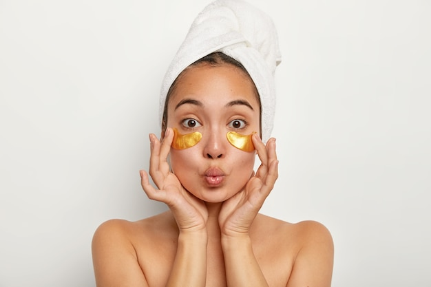 Photo of lovely female model applies yellow pads under eyes for reducing wrinkles, has anti aging procedures, keeps lips folded, stands shirtless indoor, wrapped towel on head. cosmetology concept