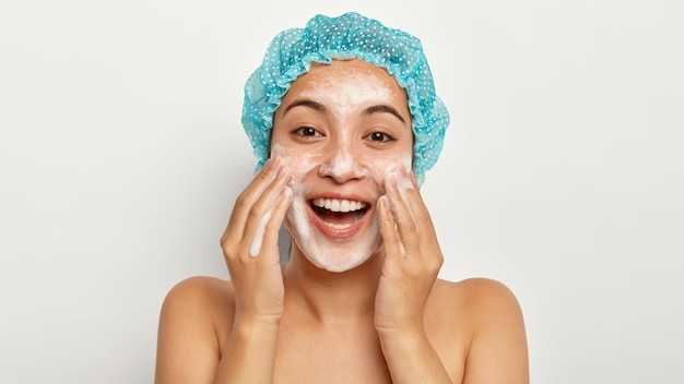 Photo of lovely female model with happy expression, washes face with foaming cleanser, wears wateproof showercap, pampers skin, stands shirtless, looks straightly. facial treatment