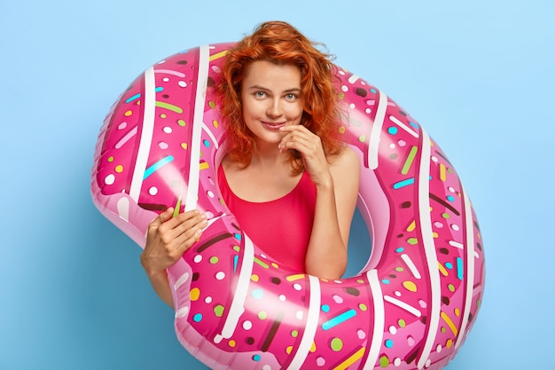 Photo of lovely ginger woman looks happily, poses inside of rubber swim ring, dressed in swimwear, rests at seaside