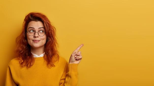 La foto dell'adorabile donna rossa punta il dito indice da parte, mostra il promo a destra, sembra con un'espressione interessante, ha i capelli rossi ondulati
