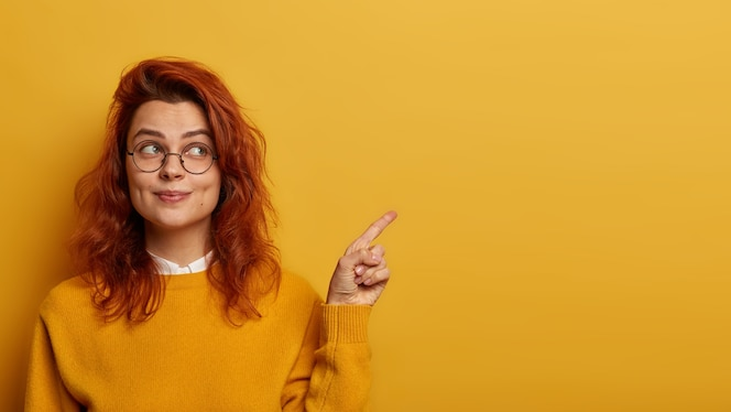Photo of lovely ginger woman points index finger aside, demonstrates promo on right, looks with interesting expression, has wavy red hair