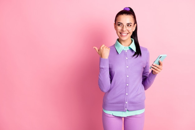 Photo of lovely girl hold telephone direct finger empty space toothy smile wear specs violet cardigan isolated pink color background