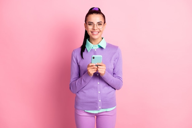 Photo of lovely girl hold telephone look camera toothy smile wear spectacles violet cardigan isolated pink color background
