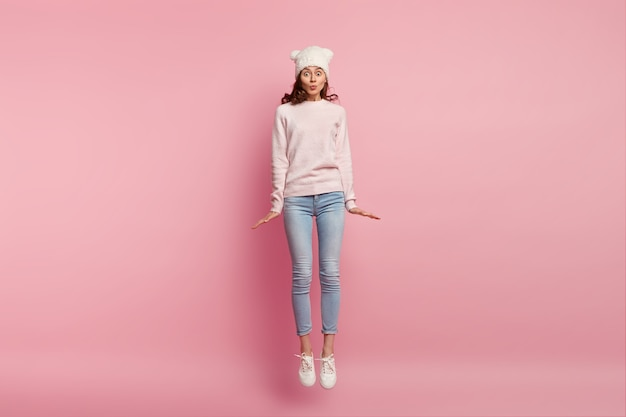 Photo of lovely girl jumps over in air against pink space, wears hat, sweater, jeans and sneakers, keeps lips folded