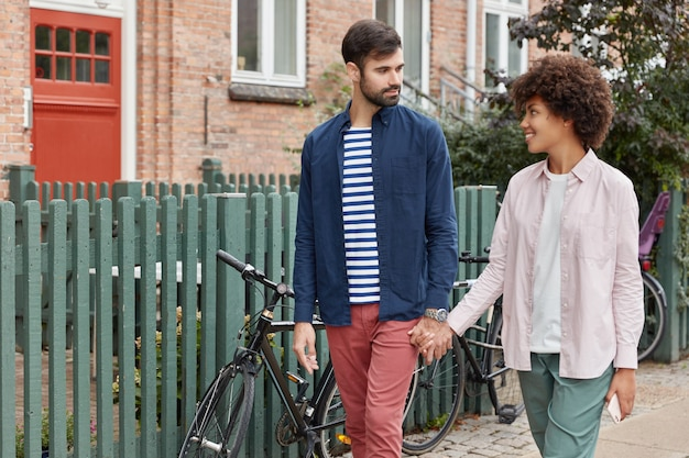 Photo of lovely interracial couple have outdoor walk, keep hands together and look at each other with love
