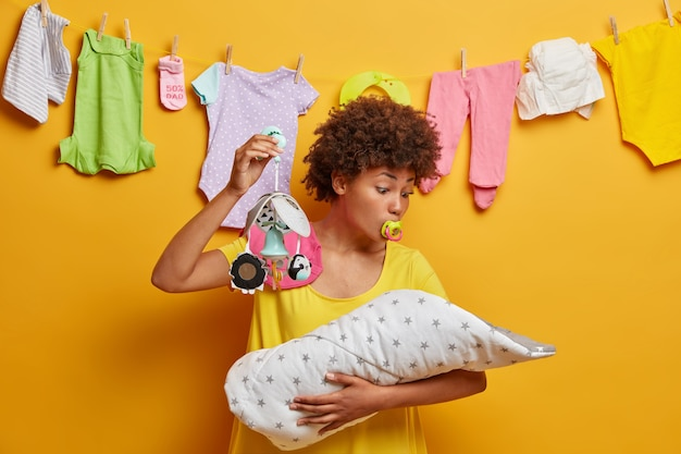 Photo of lovely mommy looks at baby and tries to sooth naughtly newborn, shows mobile and sucks nipple, nurses infant, plays with little daughter, stands over yellow wall with washed clothes