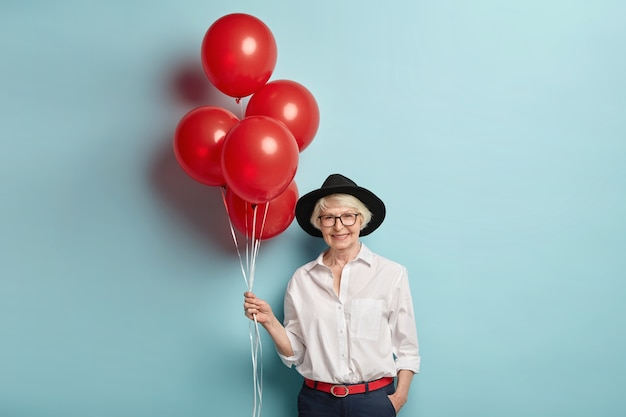 Photo of lovely old woman has fun on party with people of same age, holds bunch of air balloons, wears stylish hat, white shirt and black trousers, poses over blue wall, celebrates birthday
