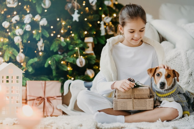 Photo of lovely small child sits crossed legs on floor, pets pedigree dog received christmas presents from parents celebrate new year together. kid enjoys holiday with jack russell terrier opens gifts