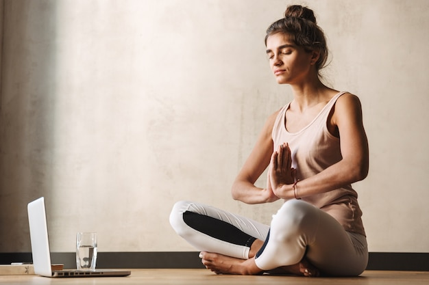 Photo of lovely woman in sportswear meditating with namaste gesture and using laptop while doing yoga on floor at home