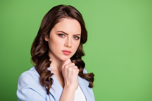 Photo of lovely woman wavy hairdo finger chin look camera wear blue blazer isolated green color background