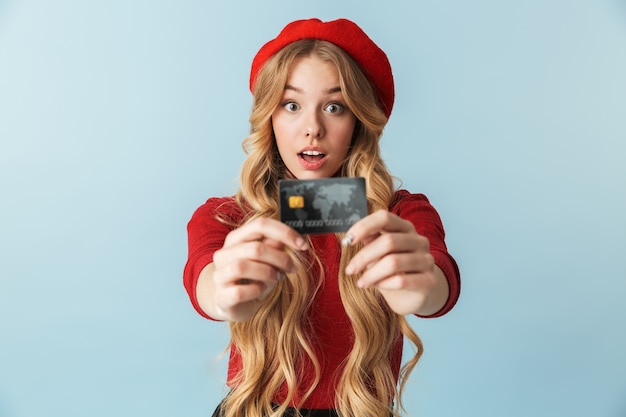 Photo of lucky blond woman 20s wearing red beret holding credit card isolated