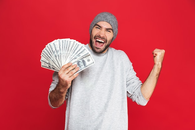 Photo of lucky guy 30s in casual wear rejoicing and holding cash money isolated