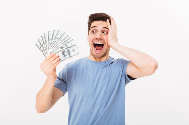 Photo of lucky rich guy in casual t-shirt screaming and rejoicing his money prize in cash, isolated over white wall