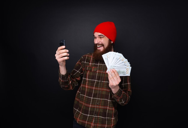 Photo of lucky smiling guy celebrating victory after making bets using gambling mobile application on his phone.