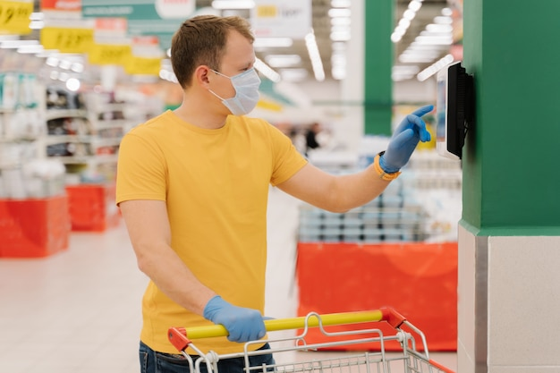 Photo of male consumer uses touchscreen in shop, checks price, poses with shopping cart, wears disposable mask and gloves