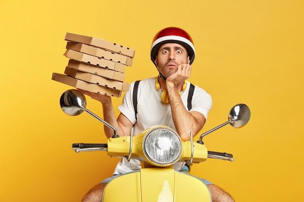 Photo of male deliveryman with helmet driving yellow scooter while holding pizza boxes