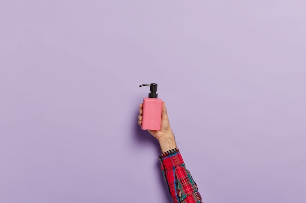 Foto della mano maschile con flacone spray di sapone liquido antibatterico