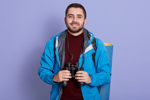 Photo of male vacationist has active rest, carries rucksack with rolled up rag, wears casual tourist clothes, uses binoculars. backpacking, traveling, resting concept