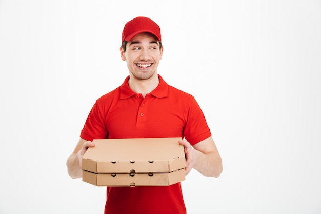Photo of male worker from delivery service in red t-shirt and cap holding two takeaway pizza boxes and looking aside on copyspace, isolated over white space