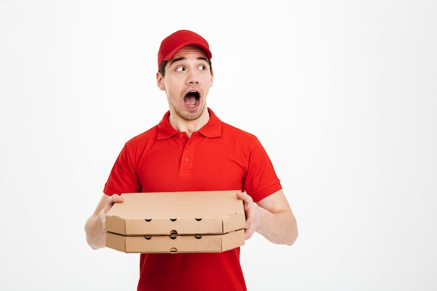 Photo of male worker from delivery service in red t-shirt and cap holding two takeaway pizza boxes and looking aside on copyspace with surprise, isolated over white space