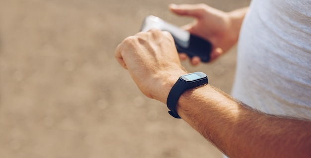 Photo of man hands touching phone and setting configuration generic design smart watch
