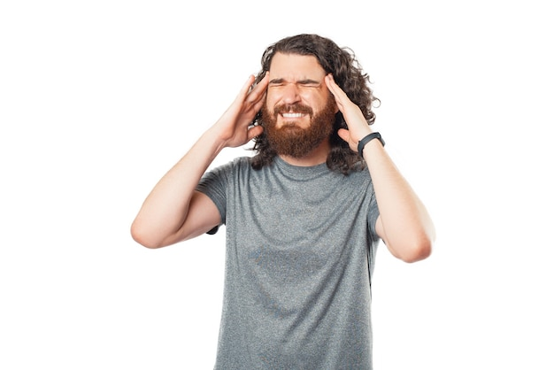 Photo of man heaving headache over white background, frustrated man