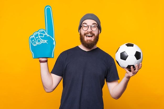 Photo of a man holding a fan glove and a soccer ball is smiling