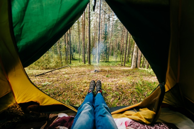 Photo of a man legs in blue jeans and sneakers laying in tourist tent with a view of the forest and fire with smoke in sunny summer day.