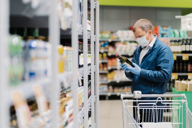 Photo of man in protective medical mask and rubber gloves to prevent coronavirus, poses in supermarket, holds glass bottle of alcoholic drink, reads label, makes shopping during quarantine time