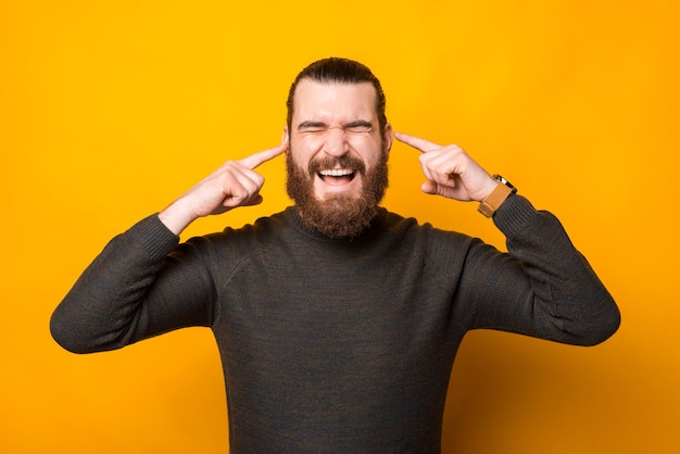 Photo of man putting fingers in ears and dont listen anything