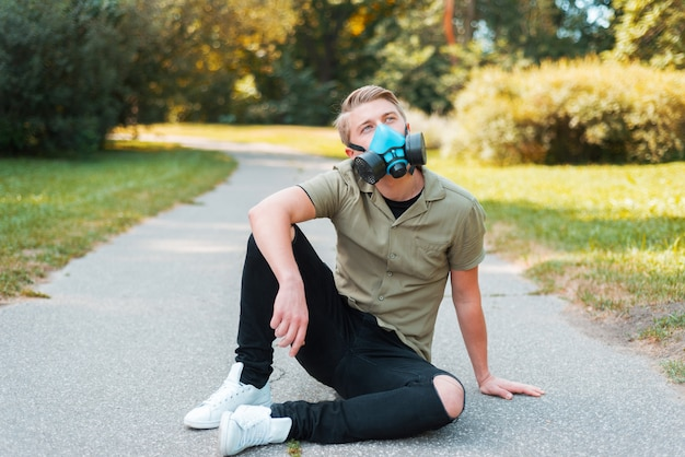 Photo of man wearing facial respirator outdoor in park and looking away.