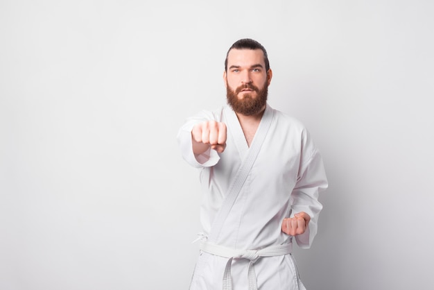 Photo of man with beard wearing taekwondo uniform training over white wall