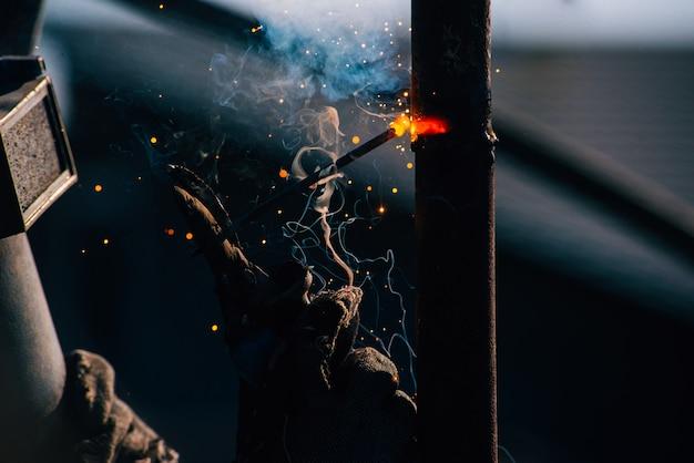 Photo of man working with welder steel using electric welding machine outdoor
