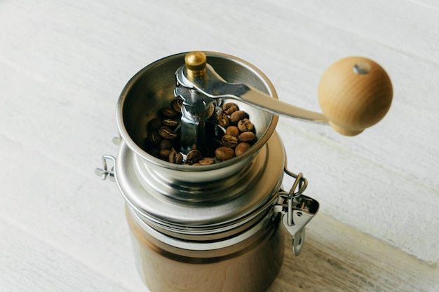 Photo of manual coffee grinder with coffee beans on white wooden table