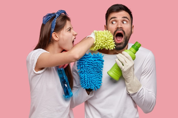 Photo of married husband and wife clean house together, pose with washing agent, sponges, wear casual outfit