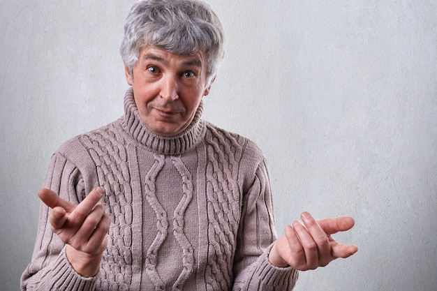 A photo of mature man dressed in sweater standing over white wall having surprised expression holding his hands in front of him