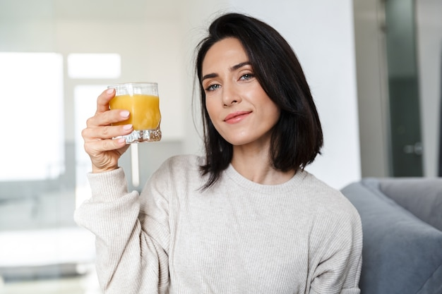 Photo of mature woman 30s drinking orange juice, while sitting on sofa in bright room