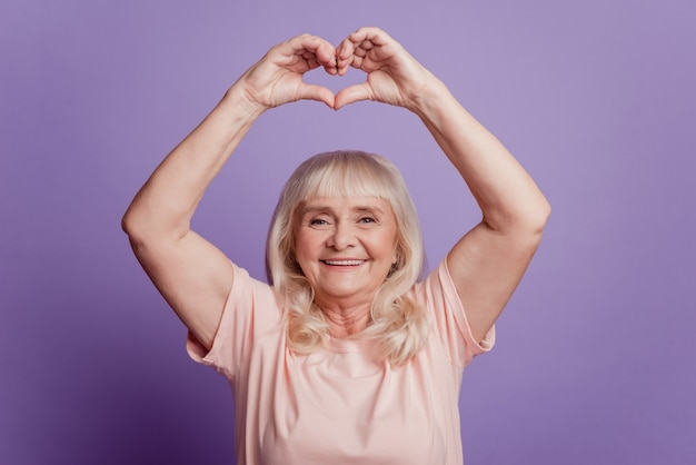 Photo of mature woman demonstrate heart fingers sign above head on violet background