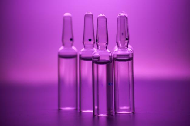 Фото медицинских ампул на темном в розовой тонировке