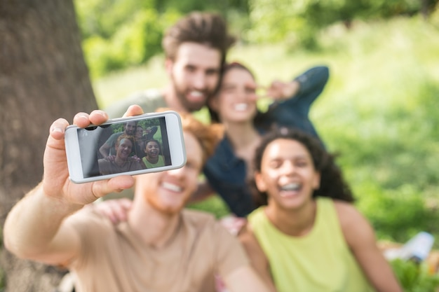 Photo for memory. red-haired young guy showing smartphone screen in outstretched hand with photo of happy friends on vacation