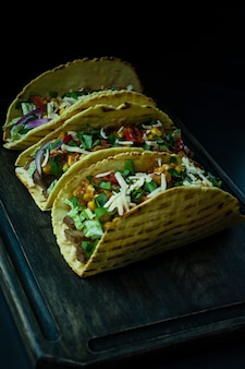 Photo of mexican tacos with meat, cheese, corn, onions and pork herbs on a wooden board. ketchup sauce and hot pepper.