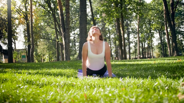 Photo of middle aged woman practicing yoga or fitness on fresh green grass at park. female physical and mental health. person in meditation and harmony pf body and soul