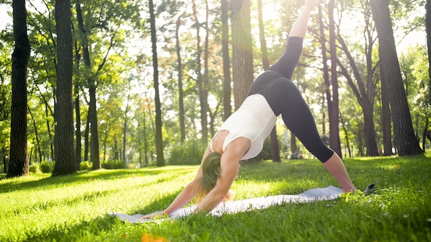 Photo of middle aged woman in sportrs clothes practicing yoga outdoors at park. middle aged woman stretching and meditating at forest