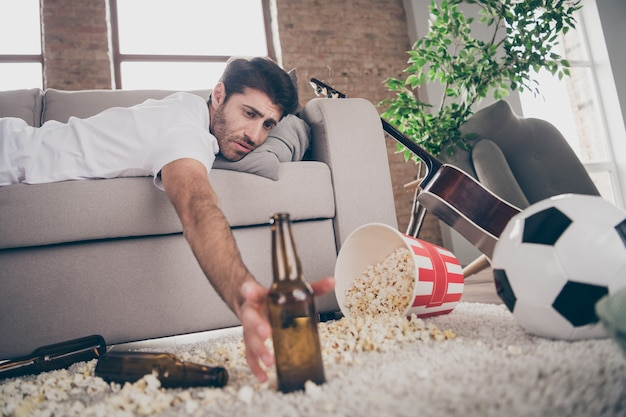 Photo of mixed race boozer guy lying sofa taking beer bottle popcorn on floor had crazy entertainment suffering after party hangover morning headache messy flat indoors