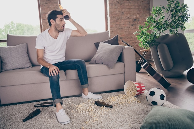 Photo of mixed race guy sitting carpet leaning sofa hold beer bottle on forehead popcorn floor had crazy stag party suffer hangover morning headache messy dirty flat indoors