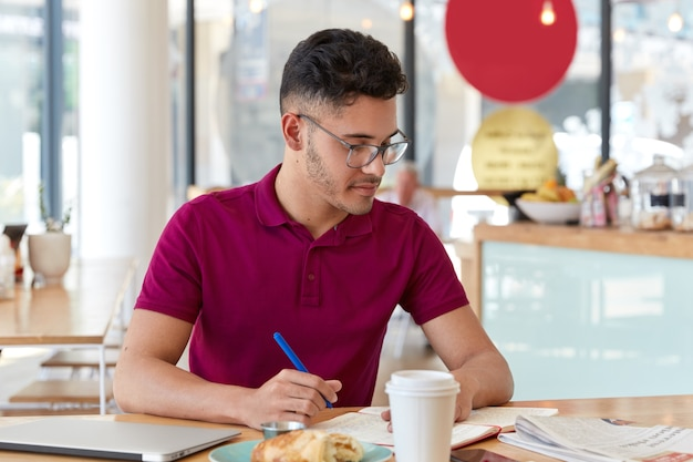 Photo of mixed race male student writes necessary information in notepad from daily newspaper, creates simmilar article, sits indoor against cafe interior, drinks take out coffee, learns indoor