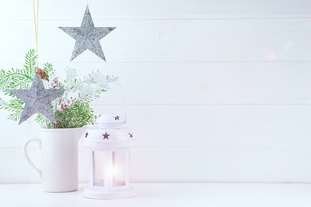 Photo mock up with pine branches in vase, stars and lantern on white wood